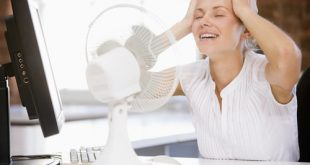 Donna in ufficio si rinfresca dal caldo con un ventilatore