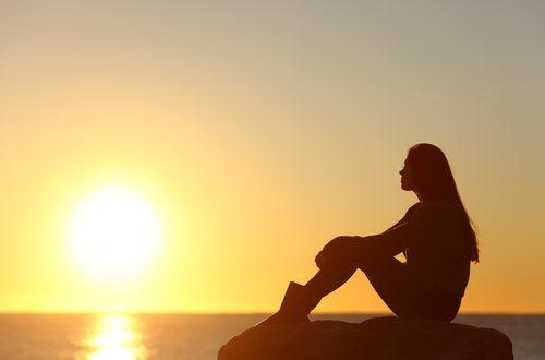 Ragazza che guarda il tramonto sul mare
