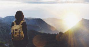 Ragazza con zaino sulle spalle ammira il panorama naturale