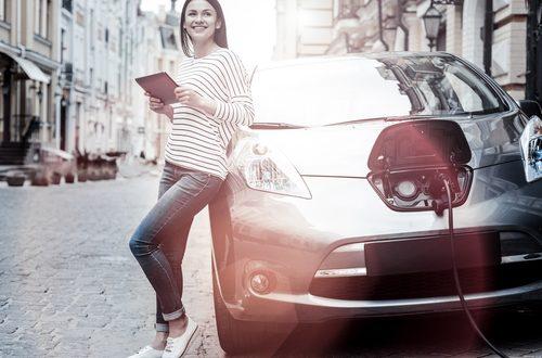 donna con auto elettrica e tablet