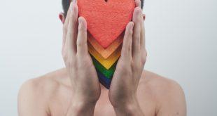 Ragazzo tiene in mano cuori con i colori del pride