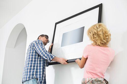 coppia appende quadro alla parete