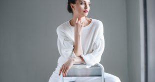 donna castana con maglia e pantaloni bianchi